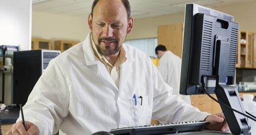 Man in lab coat looking a computer monitor